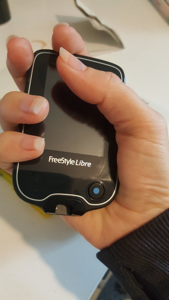 hand holding FreeStyle libre meter